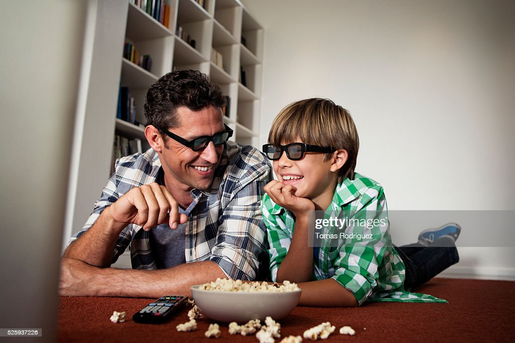 Father and son (6-7) watching tv on floor : Stock Photo
