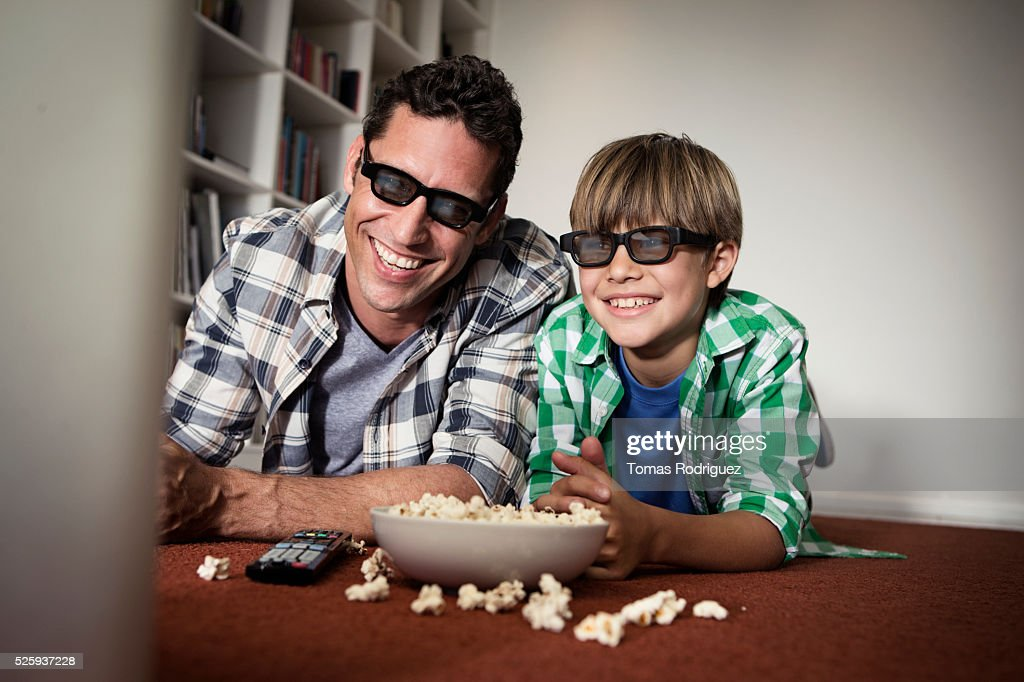 Father and son (6-7) watching tv on floor : Foto de stock