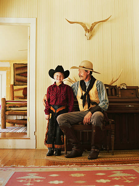 Father and son (7-9) wearing cowboy clothing in living room