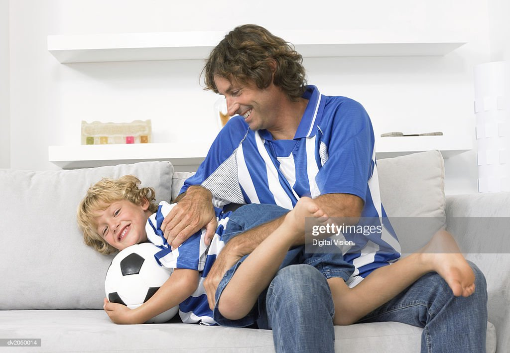 Father and Son Wearing Football Strips, Sitting on a Sofa and Playing Together : Stock Photo