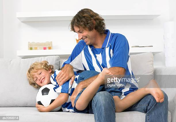 Father and Son Wearing Football Strips, Sitting on a Sofa and Playing Together