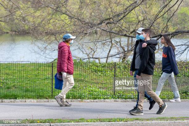 A father and son wearing protective masks walk arm in arm in Central Park as temperatures rose amid the coronavirus pandemic on April 25 2020 in New...