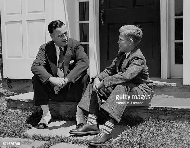 father and son wearing suits sitting out of house - {{ contactusnotification.cta }} stockfoto's en -beelden