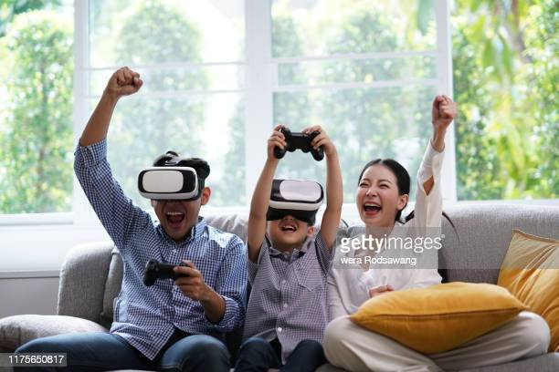 father and son wearing the virtual reality glasses playing video game - leisure games ストックフォトと画像