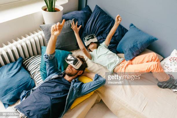 father and son wearing vr glasses lying down at home - simulatore di realtà virtuale foto e immagini stock