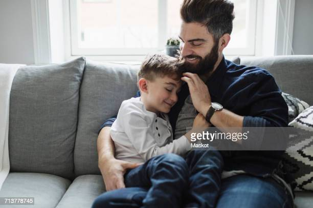 Father and son while sitting on sofa at home