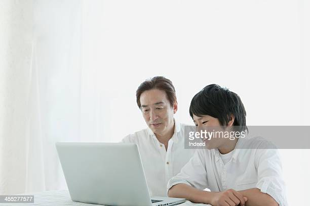 father and son who uses personal computer - side by side stock photos and pictures