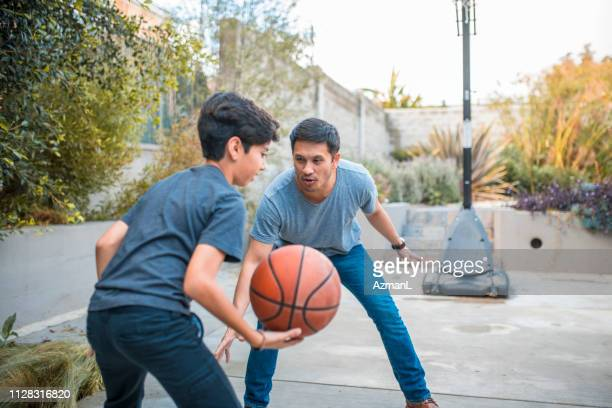 father and son with arms raised playing basketball - sports activity stock pictures, royalty-free photos & images