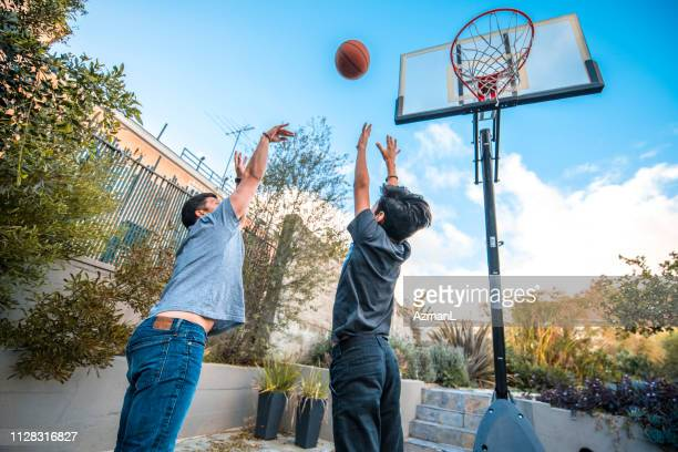 father and son with arms raised playing basketball - shooting baskets stock pictures, royalty-free photos & images
