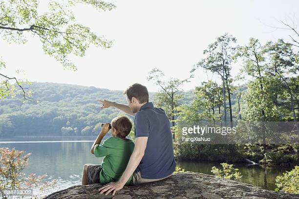 father and son with binoculars looking at view in nature - aiming stock pictures, royalty-free photos & images
