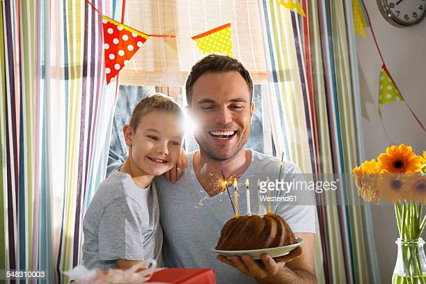 Father and son with birthday cake