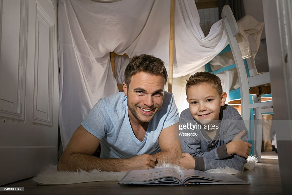 Father and son with book lying on the floor in self-made tent at home  sc 1 st  Getty Images & Father And Son With Book Lying On The Floor In Selfmade Tent At ...