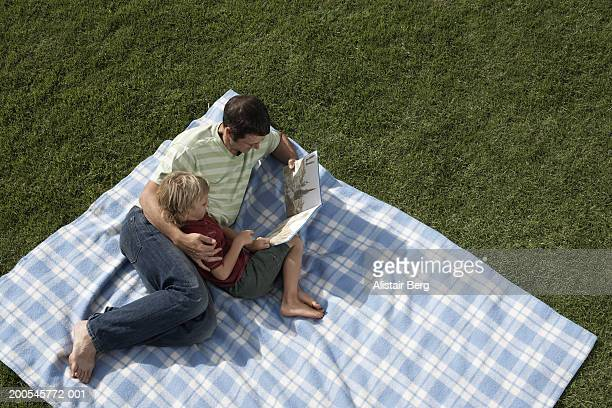 Father and son (6-8) with book on picnic blanket