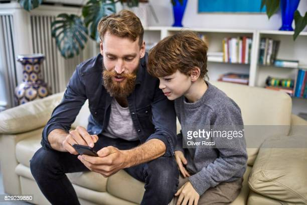 Father and son with cell phone on sofa