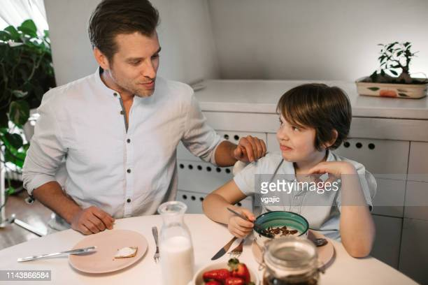 father and son with cochlear implant having healthy breakfast - cochlear implant stock pictures, royalty-free photos & images