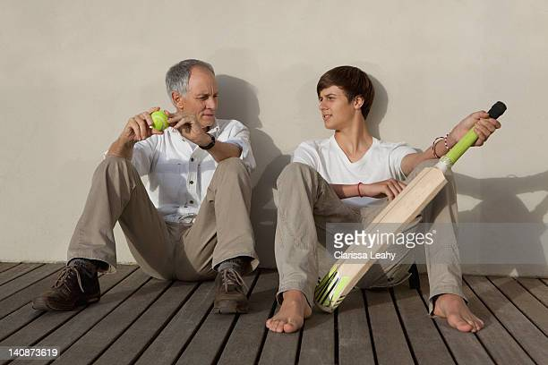 father and son with cricket bat on patio - teen boy barefoot stock photos and pictures