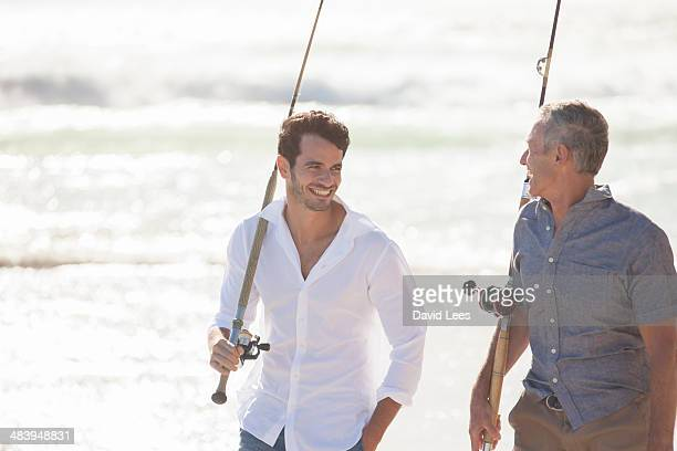 Father and son with fishing rods on beach