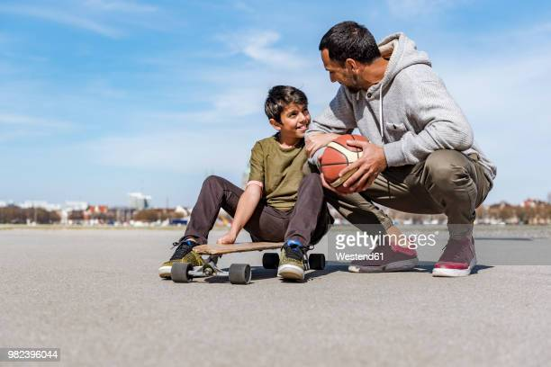 Father and son with longboard and basketball outdoors