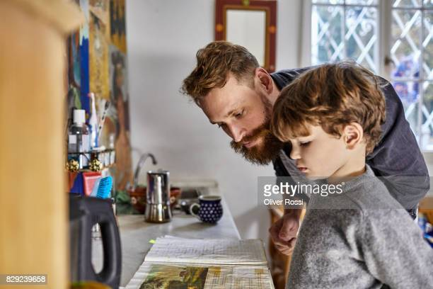Father and son with old-fashioned book in kitchen