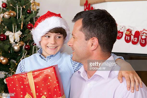 Father and son with present next to Christmas tree