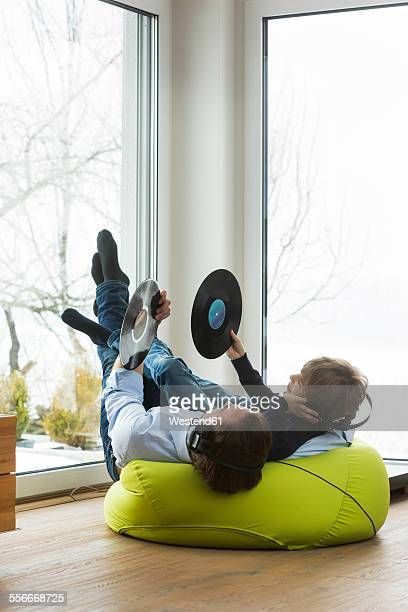 Father and son with records in living room listening music