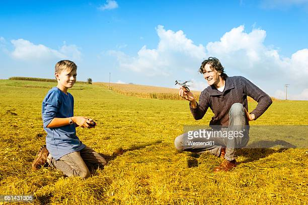 father and son with remote-controlled helicopter in meadow - remote control helicopter stock photos and pictures