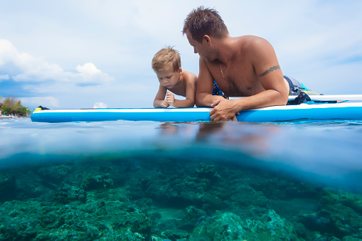Father and son with surf board in ocean,Bali,Indonesia - gettyimageskorea