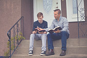 father son sit read gods word