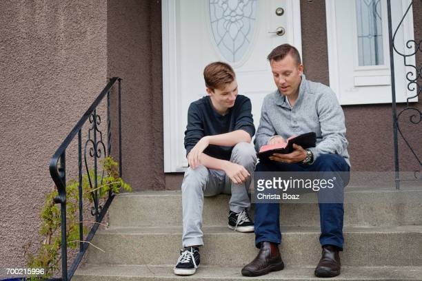 father and son with the bible - the god father stock photos and pictures
