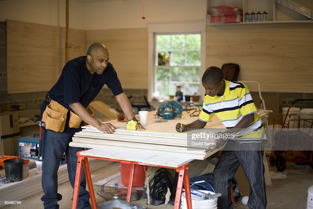 Father and son working in garage : Stock Photo