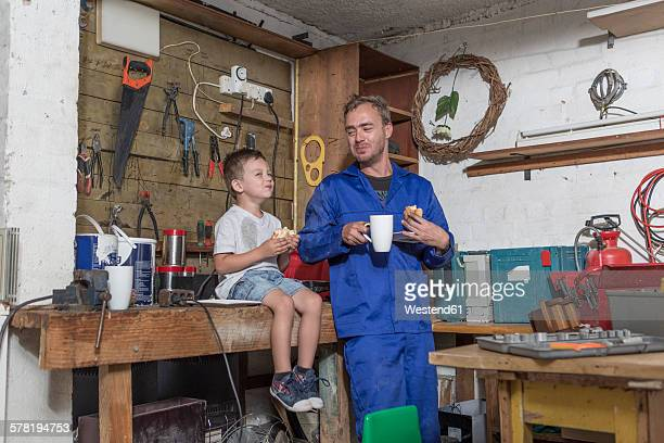 Father and son working in home garage having lunch break