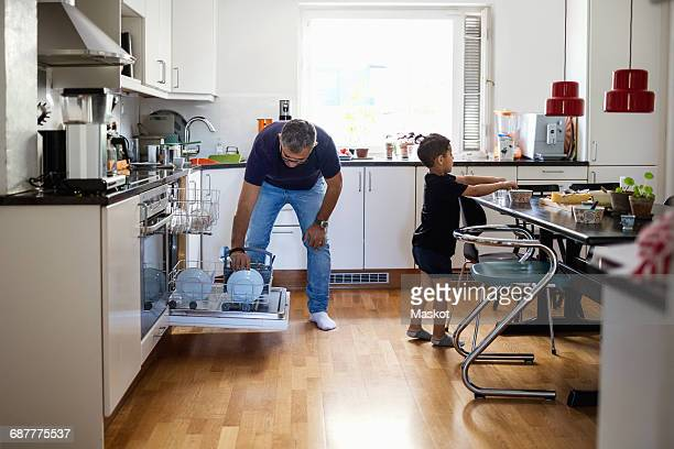 Father and son working in kitchen at home