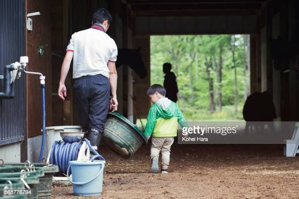 Father and son working in the horse stable together