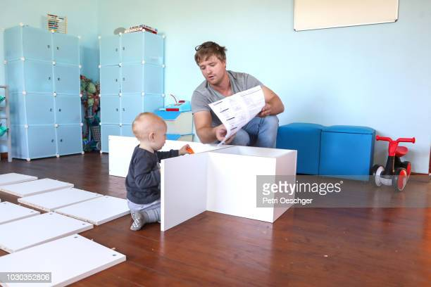 a father and son working on a d.i.y project at home. - instruction manual stock photos and pictures