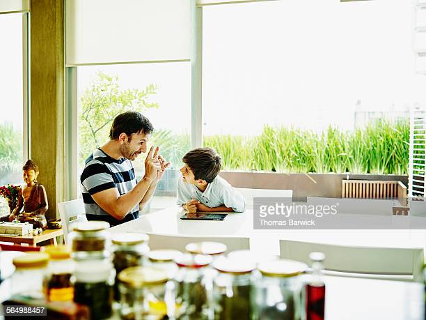 Father and son working on digital tablet in kitche