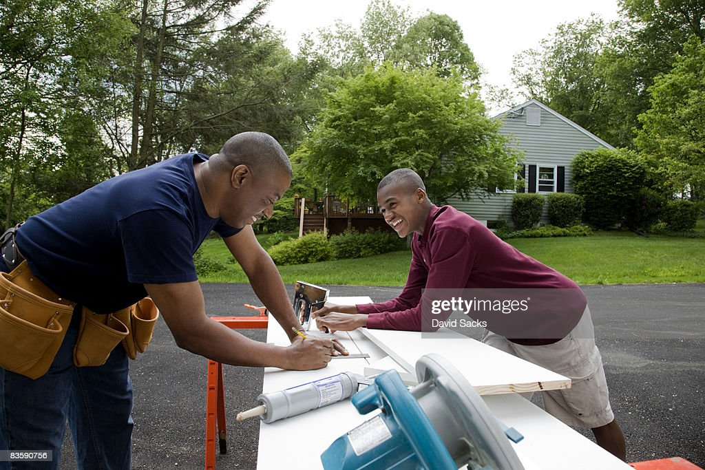 Father and son working on house : Stock Photo