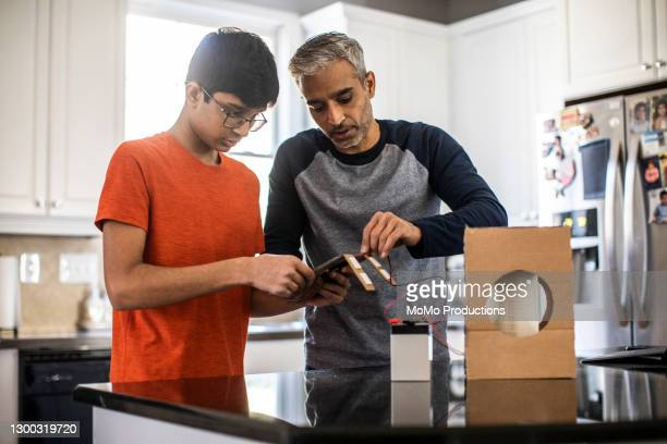 father and son working on school science project - concentration stock pictures, royalty-free photos & images