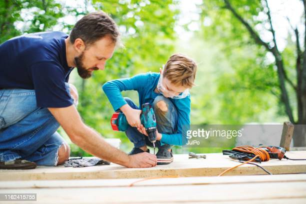father and son working togethe - tree house stock pictures, royalty-free photos & images