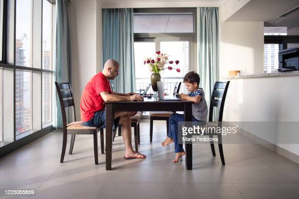 father and son working/studying distantly from home - dubai stock pictures, royalty-free photos & images