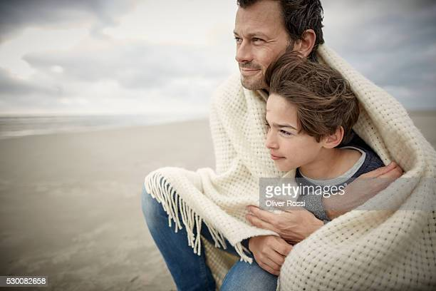 Father and son wrapped in a shawl on the beach