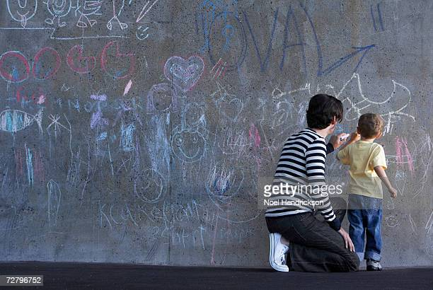 father and son (3-4 years) writing in chalk on wall - 25 29 years stock pictures, royalty-free photos & images