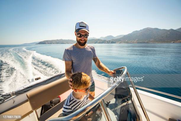 father and son yachting - nautical vessel stock pictures, royalty-free photos & images