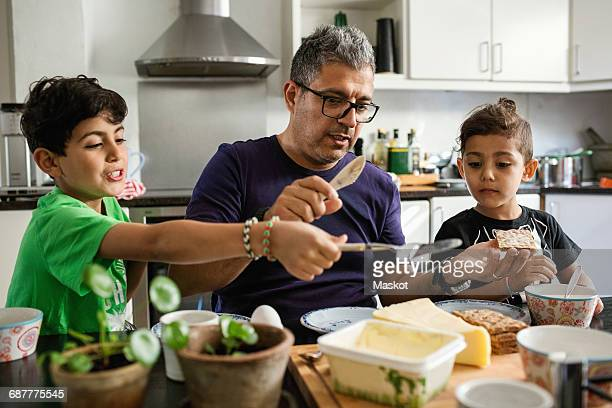 father and sons applying butter on crackers at dining table - muslim boy stock photos and pictures