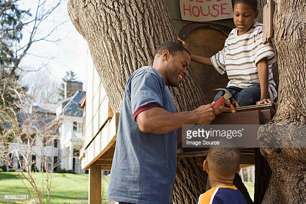 father and sons building tree house - tree house stock pictures, royalty-free photos & images