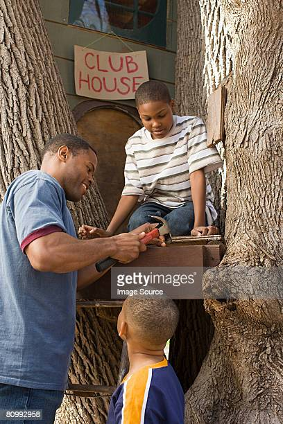 Father and sons building tree house