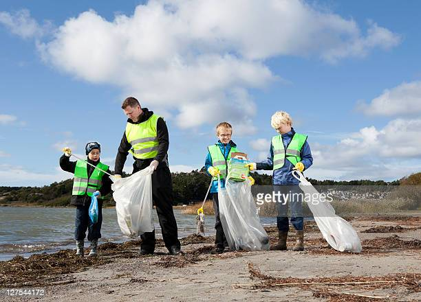 Father and sons cleaning beach