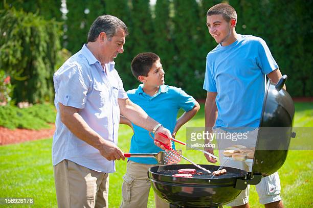 Father and sons grilling outdoors