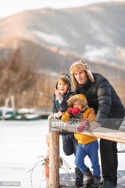 Father and sons having winter fun in the lake