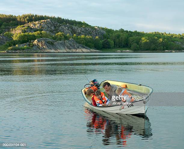 Father and sons (9-13) in rowing boat, fishing