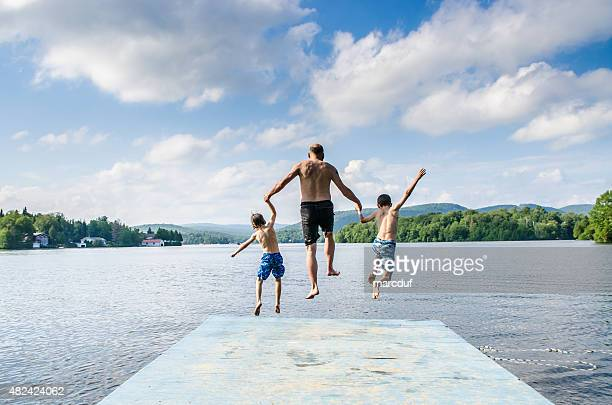 Father and sons jumping in lake